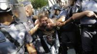 Police in Sao Paulo apprehend a protestor