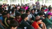 Cambodian migrant workers wait to get on buses