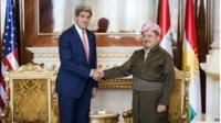 Kurdish President Massoud Barzani, right, shakes hands with US Secretary of State John Kerry