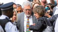 Veteran entertainer Rolf Harris, centre, accompanied by his daughter Bindi, background left and niece Jenny, centre right