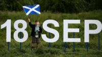 "A man holding a Saltire flag stands next to giant letters which says ""18 Sep""."