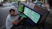 Thiago Mundano painting a trash cart