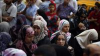 Palestinians wait to withdraw cash from an ATM machine outside a bank in Gaza City