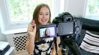 A woman making a video blog with camera