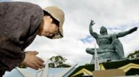 Woman prays at peace statue in Nagasaki