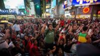 Protesters raise their arms in in New Yorks Times Square in a show of solidarity for shot US teenager Michael Brown
