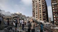 Palestinians look at the rubble of an 12-storey apartment building that collapsed after it was hit by missiles during an Israeli air strike