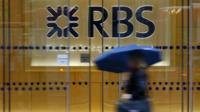 A woman walks past an RBS building