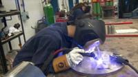 Apprentice at work in factory