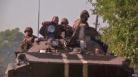 Ukrainian soldiers in a tank flee through humanitarian corridor as rebels advance