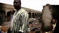 A man standing in front of damaged buildings
