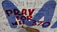 A Malaysia Airlines employee writing a message for passengers of the missing MH370 aeroplane