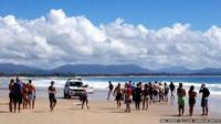 This photo taken by ABC News on 9 September 2014 shows people gathered at Australia's Clarke Beach in Byron Bay moments after the attack took place