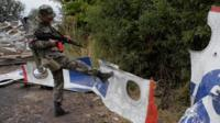 A pro-Russian separatist kicks a piece of wreckage at the MH17 crash site