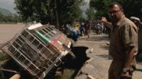 Sanjoy Majumder pointing at overturned vehicles in Srinagar