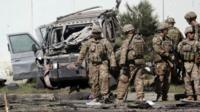 U.S. military forces inspect the site of a suicide attack near a U.S. military camp in Kabul