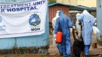 Health workers carry Ebola victim at a treatment hospital