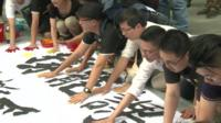 People leaving hand prints on a protest banner in Hong Kong