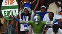 A Sierra Leone football fan with an anti-Ebola placard
