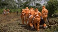 Burial team in protective clothing carrying Ebola victim in Port Loko, Sierra Leone