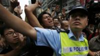 Policeman holding back protesters