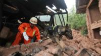 Rescuer worker and sniffer dog at damaged property