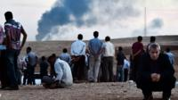 Man look on as smoke rises over Kobane