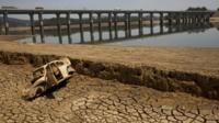 The frame of a car sits on the cracked earth at the bottom of the Atibainha dam