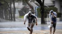 People struggle to walk against strong wind and rain caused by Typhoon Vongfong
