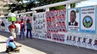 People walk pass a wall adorned with various election campaign posters