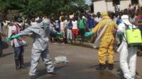 Sierra Leone burial team disinfecting themselves after removing body from street