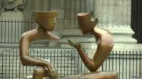 Bronze sculpture by French sculptor Etienne of two figures in conversation - part of an exhibition in the Saint-Germain district of Paris