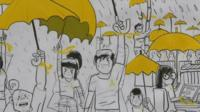 Close up of cartoon-style artwork on Hong Kong street showing protesters with yellow umbrellas