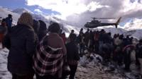 People gathering near a helicopter belonging to Nepal Army