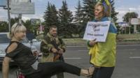 "Irina, tied to a lamppost and draped in a Ukrainian flag, and a sign that reads (in Russian) ""Ukrainian agent and baby-killer"" being kicked by a woman"