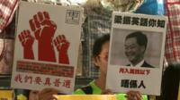 Protesters holding placards, including one with CY Leung's face on