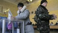Ukrainian voters cast their ballots at a polling station during parliamentary elections in Kiev
