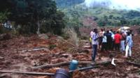 Sri Lankan residents stand at the site of a landslide