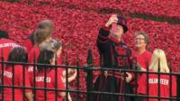 Beefeater taking selfie photograph with volunteer at poppies installation
