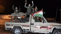Kurdish Peshmerga fighters in truck flying Kurdish flag
