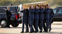 Coffin carried to a hearse