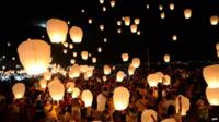 Crowds releasing paper lanterns