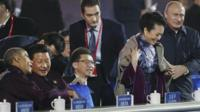 Vladimir Putin putting a coat around Peng Liyuan while seated alongside Xi Jinping and Barack Obama