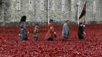 Artist Paul Cummins and servicemen walk past his creation of ceramic poppies at the Tower of London on 11 November 2014