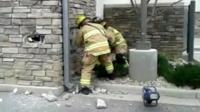 Fire fighters make hole in wall