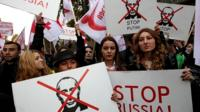 Supporters of the United National Movement Party hold anti-Putin placards during an anti-Russia rally, Tbilisi, Georgia