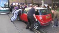Bystanders lifting car