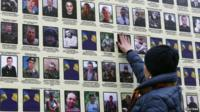 A woman touches a portrait of her husband in Kiev, on a banner with portraits of Ukrainian servicemen killed in the conflict with pro-Russian separatists in eastern Ukraine