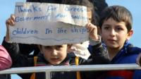 Migrant children display a sign upon their arrival at Crete