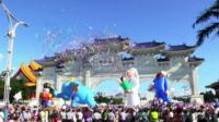 A crowd in Taipei with inflatable figures floating above as part of a celebration